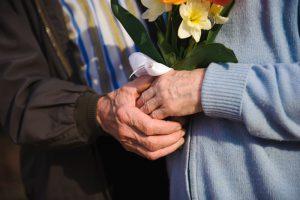 ręce starszych ludzi z kwiatkiem
